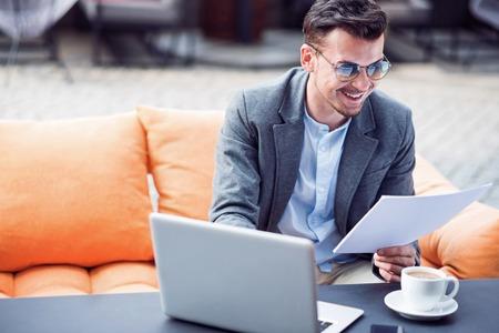 diligente: trabajador diligente. sonriente hombre de negocios alegre que trabaja con los papeles y utilizando equipo port�til mientras est� sentado en el caf�