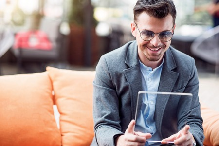 gladness: Share gladness. Joyful smiling businessman using tablet and sitting at the table while resting in the cafe