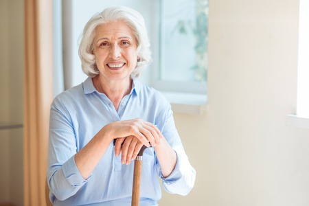 Portrait. Happy and merry senior woman sitting with crutch