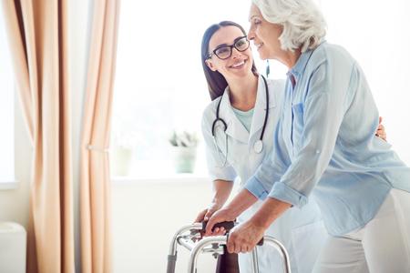 Professionelle ein. Geerntetes Bild der junge Arzt helfen, ältere Frau mit Gehhilfe Standard-Bild - 61770608