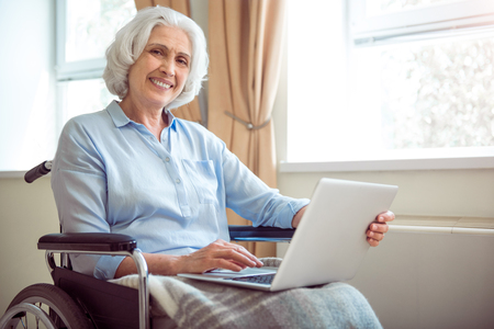 users video: Digitalization. Cheerful and positive senior woman in wheelchair using laptop
