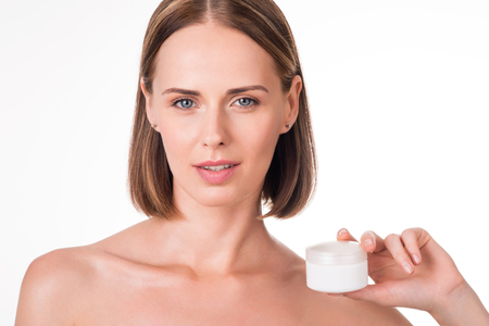 humidify: Cosmetology. Young sexy and positive woman holding jar of cream being on isolated white background