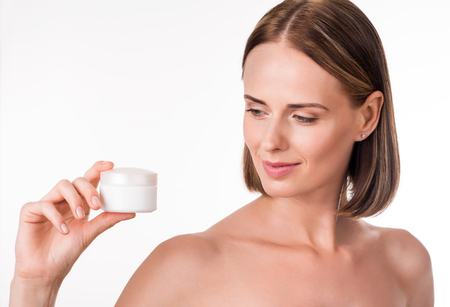 humidify: Body care. Young adult delighted and content woman holding jar of cream being on isolated white background
