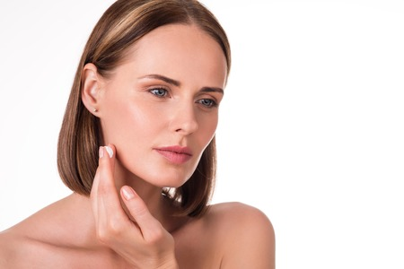 charmed: Sensitive skin. Young charmed and positive woman applying moisturizing cream on her face being on isolated white background