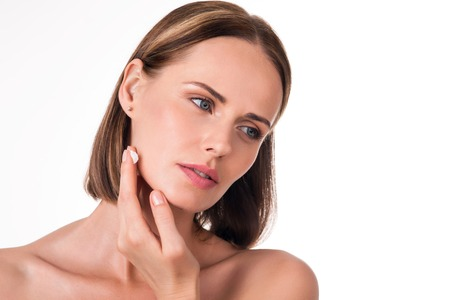 wistful: Fresh skin. Portrait of young wistful woman applying cream on her face being on isolated white background