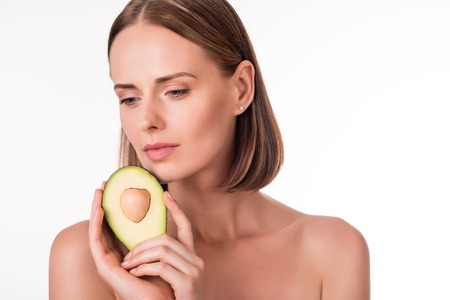 wistful: Only fruits. Wistful young woman holding avocado being on isolated white background Stock Photo