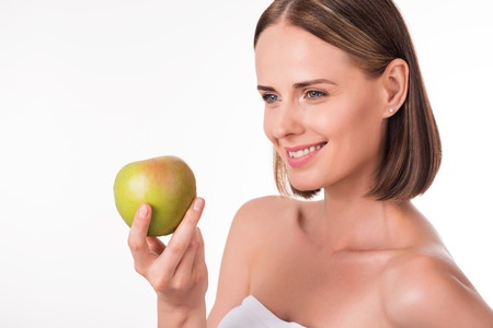 Stay positive and healthy. Happy and content young woman holding green apple being on isolated white background