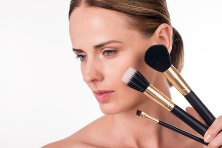 Perfect visage. Close-up portrait of wistful young woman holding makeup brushes near her beautiful face being on isolated white background