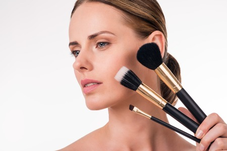 wistful: Natural. Close-up portrait of wistful young woman holding makeup brushes near her beautiful face with natural makeup being on isolated white background