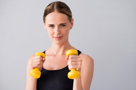 dumb: Strong one. Happy and merry young woman holding dumb bells in hands while standing on isolated grey background Stock Photo