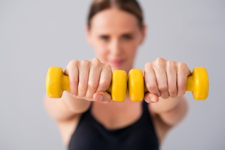 dumb bells: My lifestyle. Selective focus of young smiling woman holding dumbbells while standing on isolated grey background