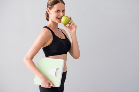Only apples. Cropped image of cheerful and smiling young woman eating green apple and holding scales while standing on isolated grey background Stock Photo
