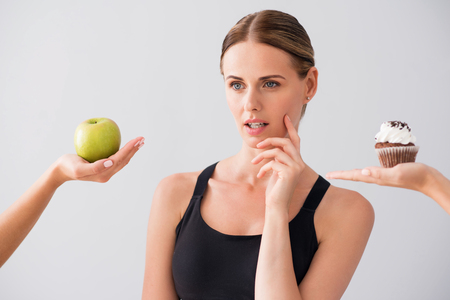 wistful: My choice. Wistful young woman choosing what to eat apple or cake while standing on isolated grey background