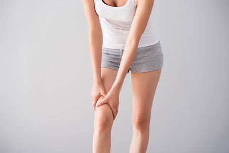 traumatic: Traumatic sport. Cropped image of young woman having legs ache being on isolated grey background Stock Photo