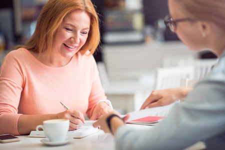 Let me see. Cheerful smiling woman sitting at the table and making notes while conducting an interview