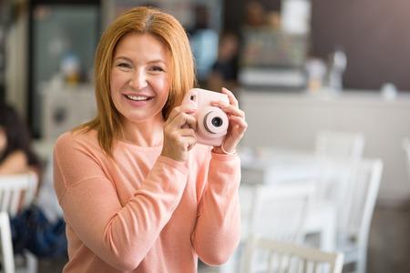 overjoyed: Joyful mood. Overjoyed beautiful senior woman holding photo camera and resting while expressing positivity