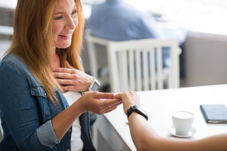 I am so happy. Positive smiling mother sitting at the table while her daughter showing her a ring Stock Photo