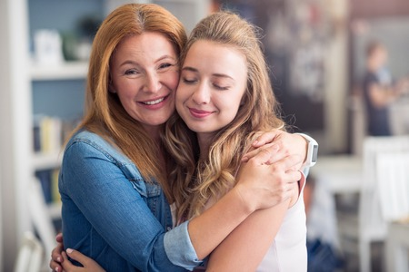 maternal: Maternal drive. Cheerful mother and daughter smiling and embracing while standing in the cafe
