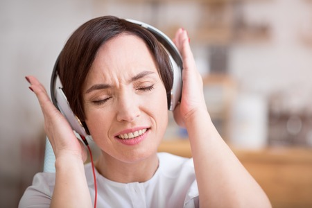 music therapy: Music therapy. Close-up portrait of delighted young woman listening music using headphones with shut eyes
