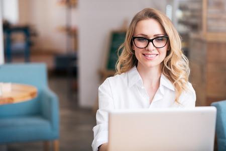 diligente: trabajador diligente. Feliz y una mujer joven con ordenador port�til mientras se trabaja y se sienta en la mesa sonriente