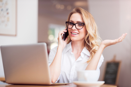 talker: Idle talker. Smiling and merry young woman talking per smart phone and using laptop while working and sitting at the table