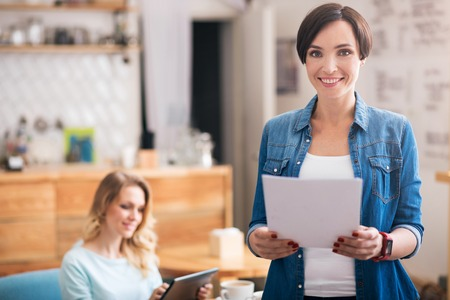 Being freelancers. Delighted and confident young woman standing with papers in foreground and cheerful woman using tablet in background