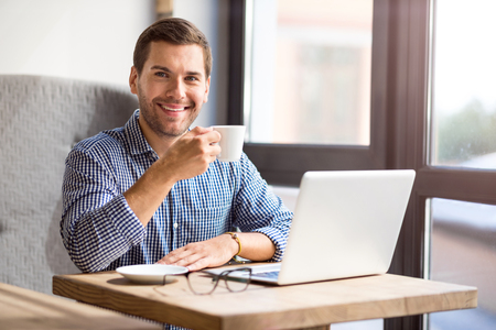 Pleasant relaxation. Joyful delighted handsome man smiling and drinking coffee while sitting at the table