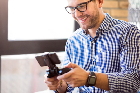 game console: Childish activity. Cheerful delighted smiling man holding game console and playing video games while relaxing Stock Photo