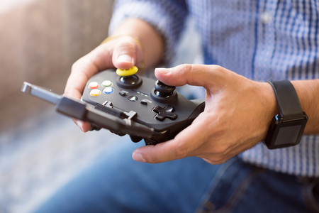 pleasant: Push it. Close up of game console in hands of pleasant man holding it while playing video games