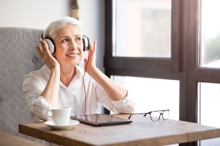 Rise your mood. Positive content senior woman sitting at the table and listening to music while resting in the cafe