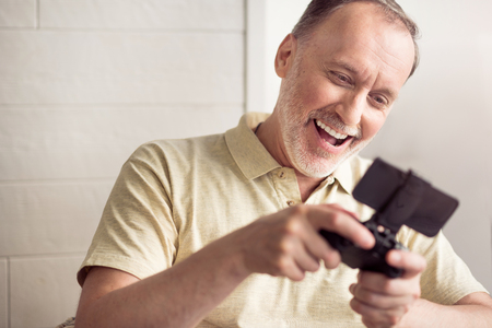 overjoyed: Have some fun. Overjoyed handsome senior man holding game console and smiling while playing video games