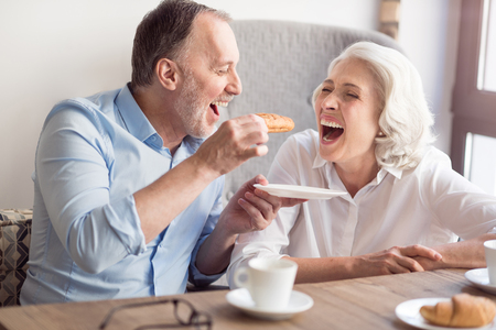 overjoyed: Happy meal. Overjoyed delighted senior couple sitting at the table and eating croissants and sitting at the table while resting in the cafe Stock Photo