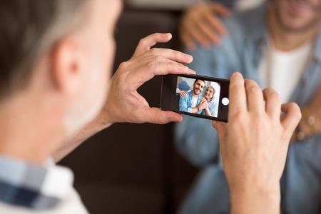 say cheese: Say cheese. Selective focus of cell phone in hands of pleasant enior man holding it and resting in the cafe with his wife and adult grandson Stock Photo