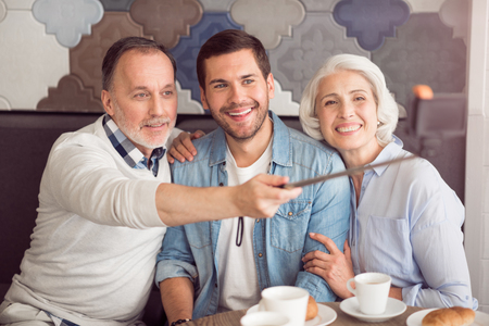 elated: Elated atmosphere. Joyful smiling senior couple and their adult son sitting at the table and making selfies while resting in the cafe