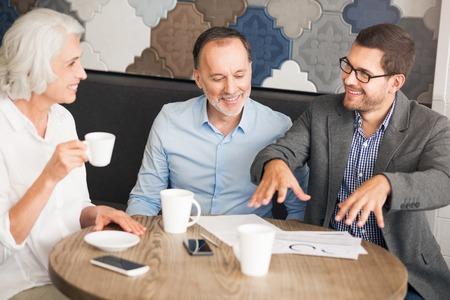 diligente: trabajador diligente. Alegre encantados gerente de ventas profesional sentado en la mesa y hablar con sus clientes
