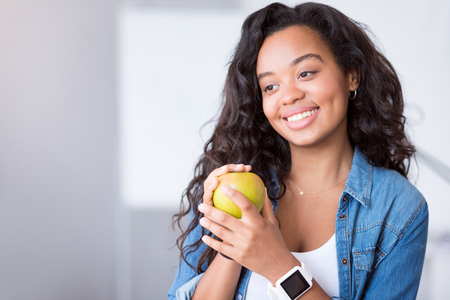expressing joy: Natural present. Positive beautiful woman holding an apple and expressing joy while smiling