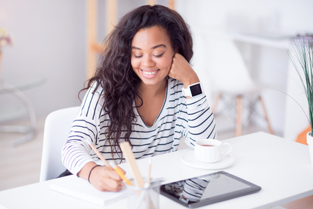 Positivity in mind. Cheerful delighted beautiful woman sitting at the table and smiling while making notes Stock Photo