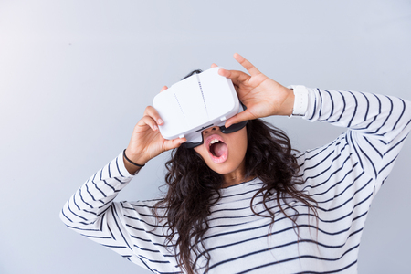 glad: New experience. Cheerful glad woman using virtual reality device while standing isolated on grey background