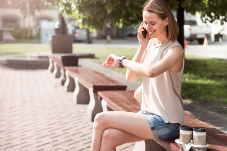 waiting phone call: Waiting for you. Cheerful young woman speaking by phone and looking at the watch