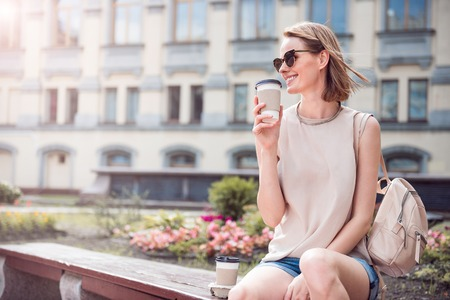 Good mood. Delighted and smiling young woman sitting and drinking coffee being outdoors