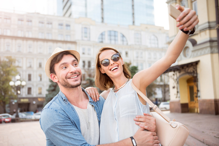 say cheese: Say cheese. Delighted and positive young tourists couple taking selfie on city street