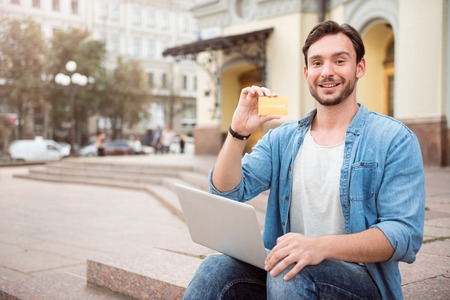 overjoyed: Convenient to pay. Overjoyed man holding gold card and laptop while sitting on steps outdoors