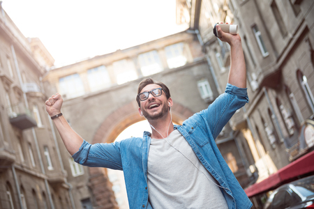absolute: Absolute happiness. Joyful good looking young man walking down the street and holding his hands up while listening to music.