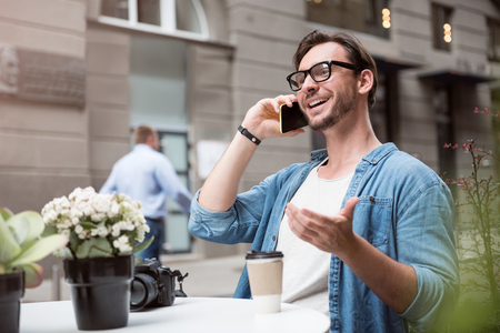 devise: Pleasant conversation. Young delighted optimistic man speaking on the cellphone and smiling while sitting at the table