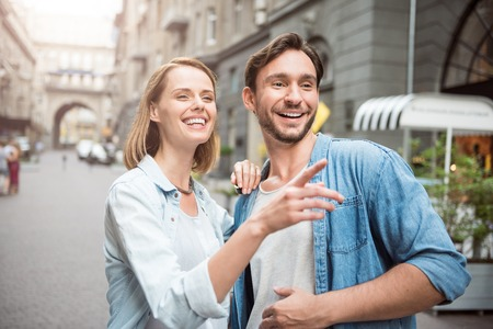 Just look. Joyful young couple standing in the street and looking forward while smiling Stock Photo