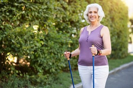 aging woman: Beautiful aging. Attractive well-fit retiree woman posing with tracking sticks on the trail
