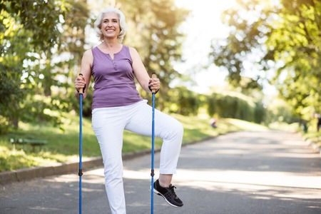 goodlooking: What a nice morning Smiley good-looking woman doing morning exercises in city park Stock Photo