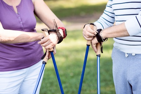 Healthy way of life. View of elderly people's hands with tracker watches on holding tracking sticks