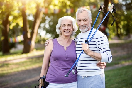 likable: Accomplished. Smiley elderly man and woman hugging each other while holding tracking sticks