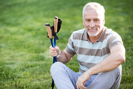 hazel eyes: Have some rest. Grey man with hazel eyes posing while sitting on green grass with tracking sticks in his habds